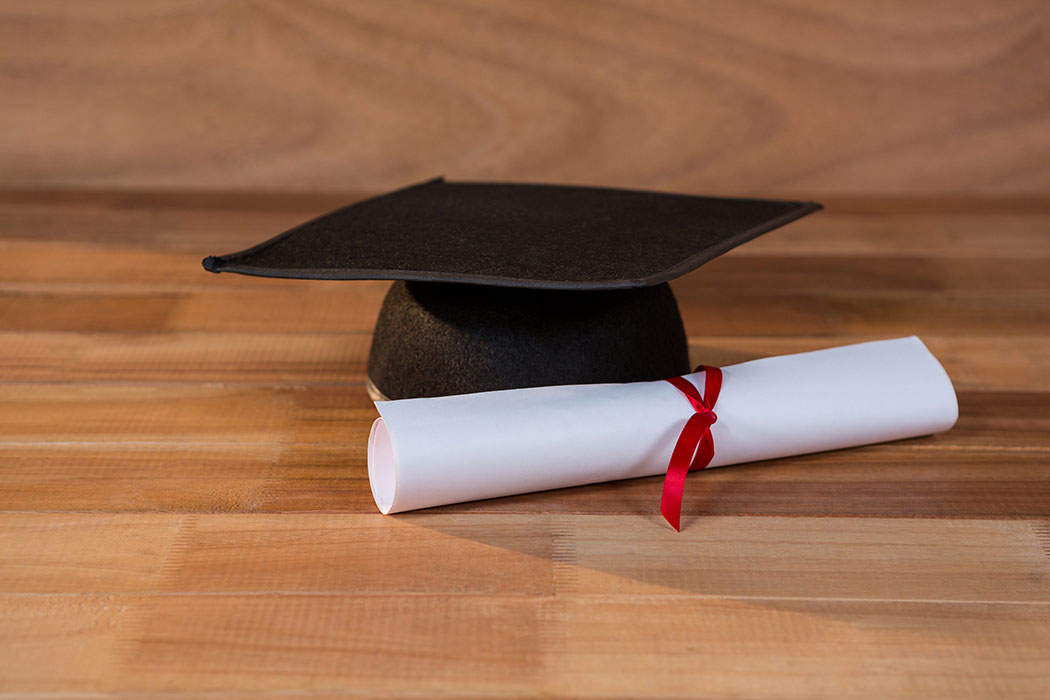 Close-up of graduation certificate with mortar board on a table